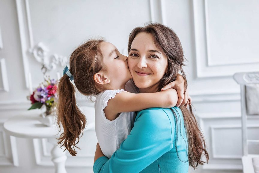 10 year old embracing and kissing her smiling beautiful mother