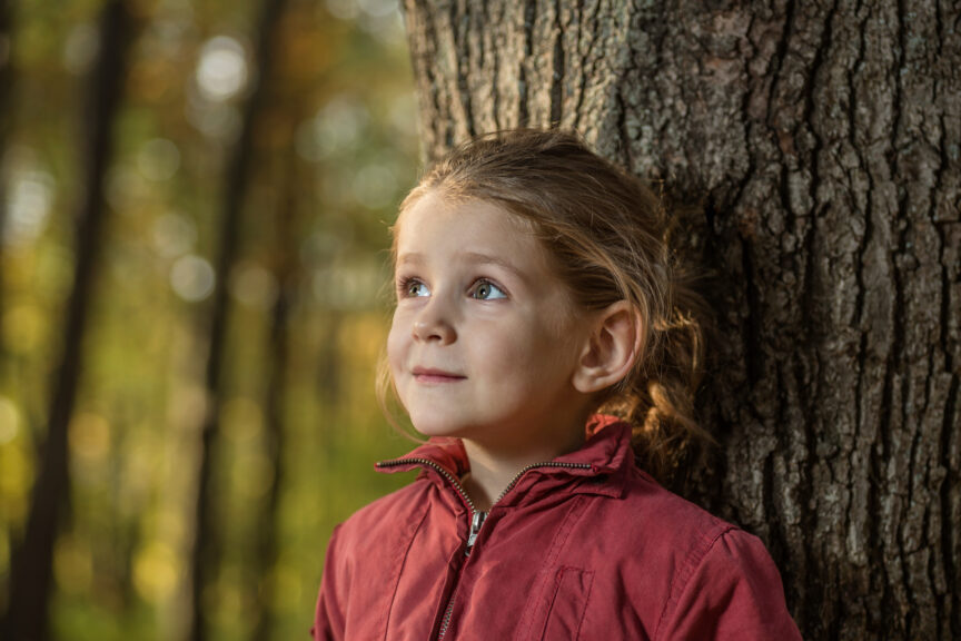 A young girl leaning against a tree trunk