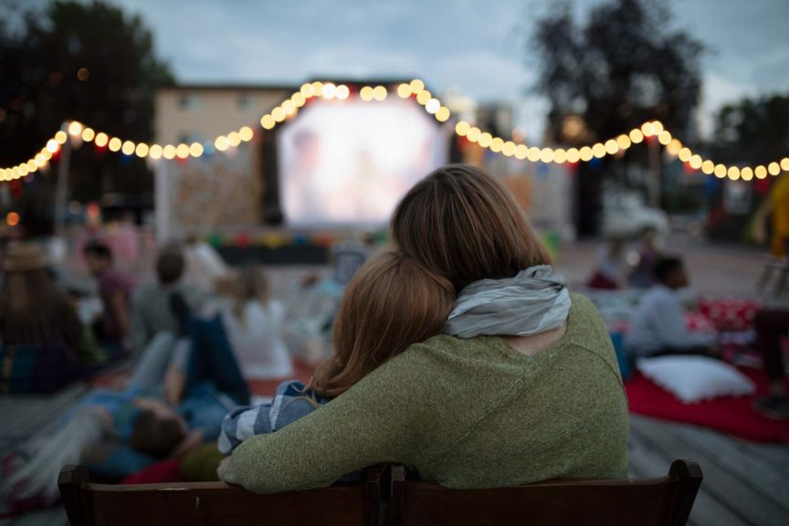 Affectionate mother and daughter at movie in the park