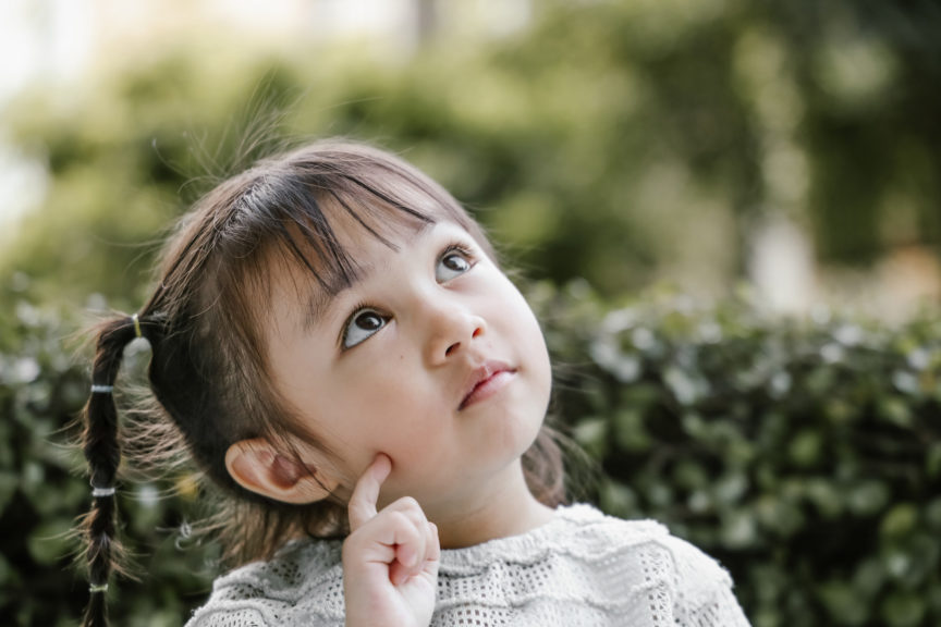 Beautiful kid playing Thinker with serious