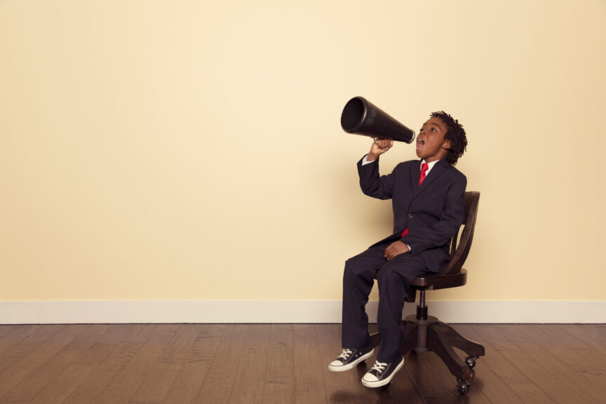 Boy-in-Business-Suit-Sitting-on-Chair-Yells-through-Megaphone