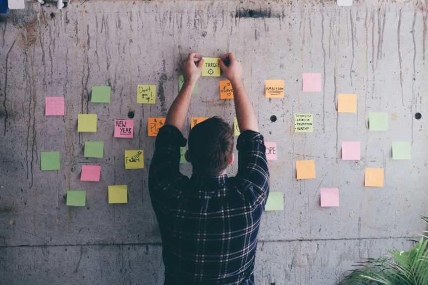 Businessman writing inspirational notes on sticky notes