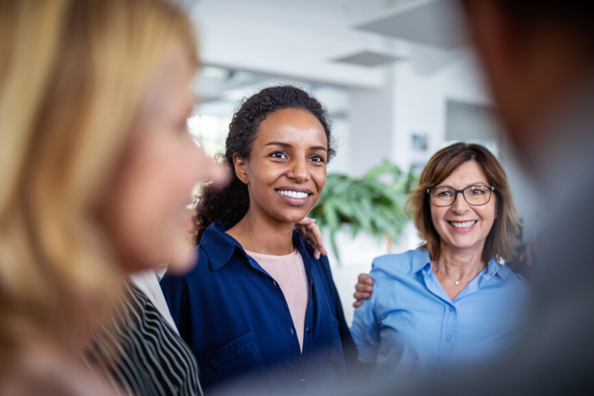 Businesswoman huddling with coworkers in office