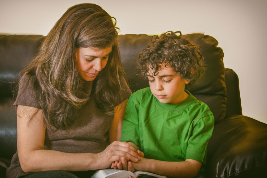 Close-Up Of Mother And Son Praying While Sitting On Sofa At Home