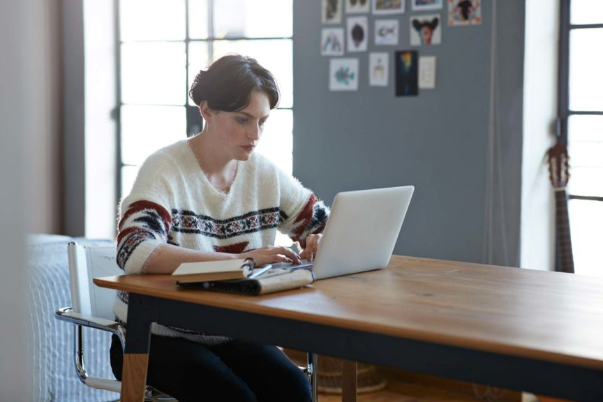 Cool young woman sitting in apartment with laptop