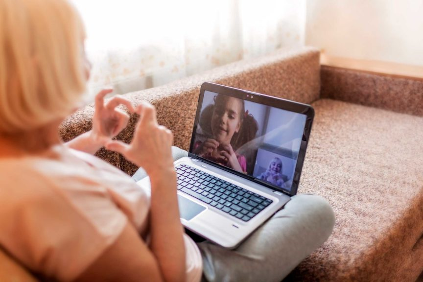Cute girl talking with her grandmother within video chat on laptop