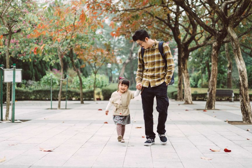 Dad and daughter strolling in park joyfully