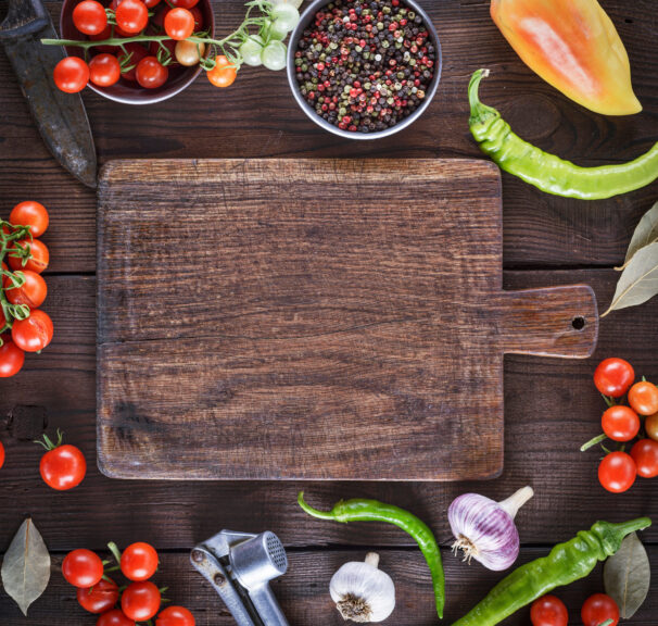 Directly-Above-Shot-Of-Cutting-Board-Amidst-Various-Ingredients-On-Table