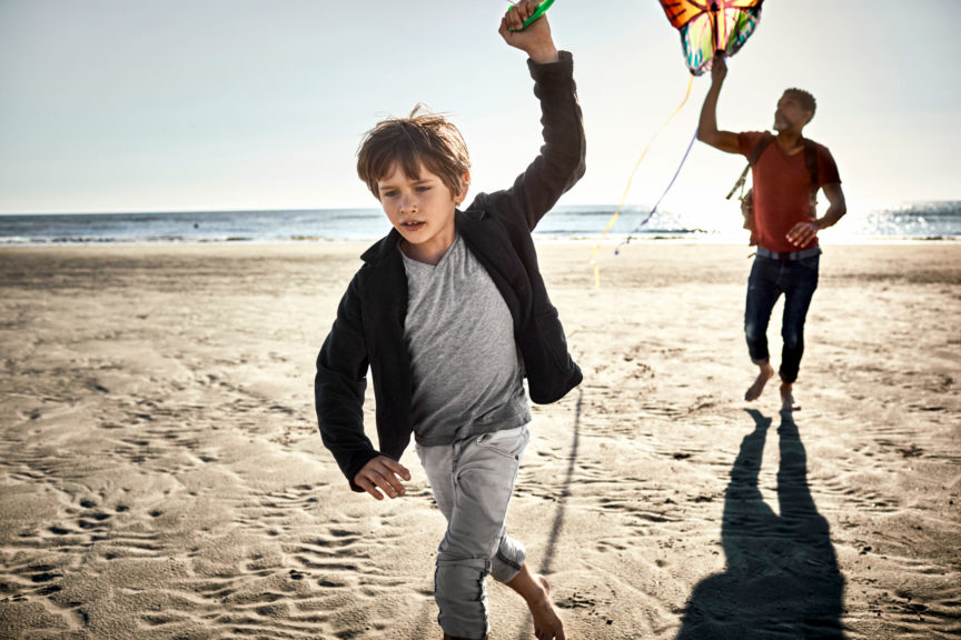 Father and son flying kite on the beach