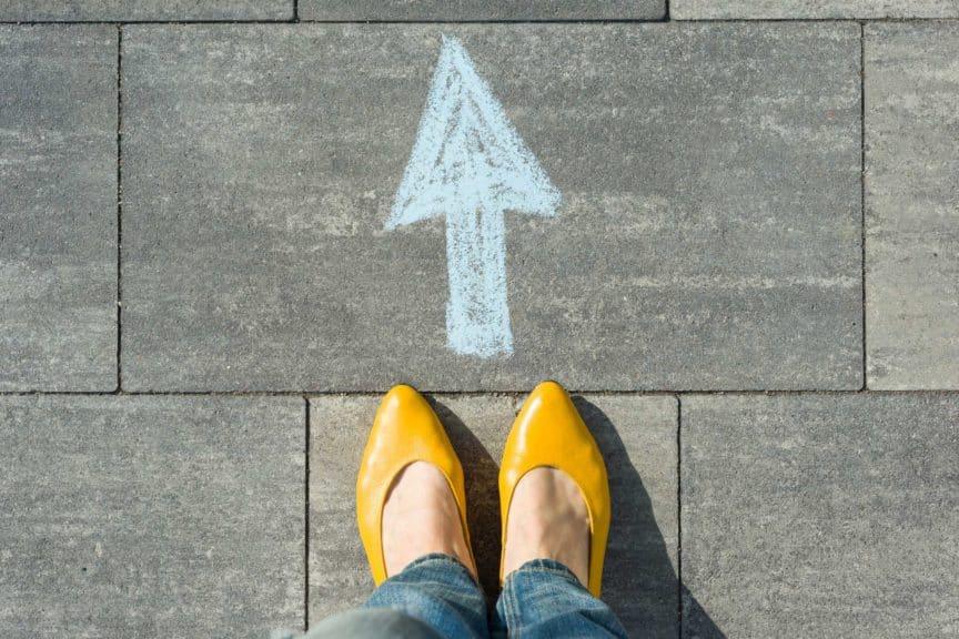 Female feet with arrow painted on the asphalt