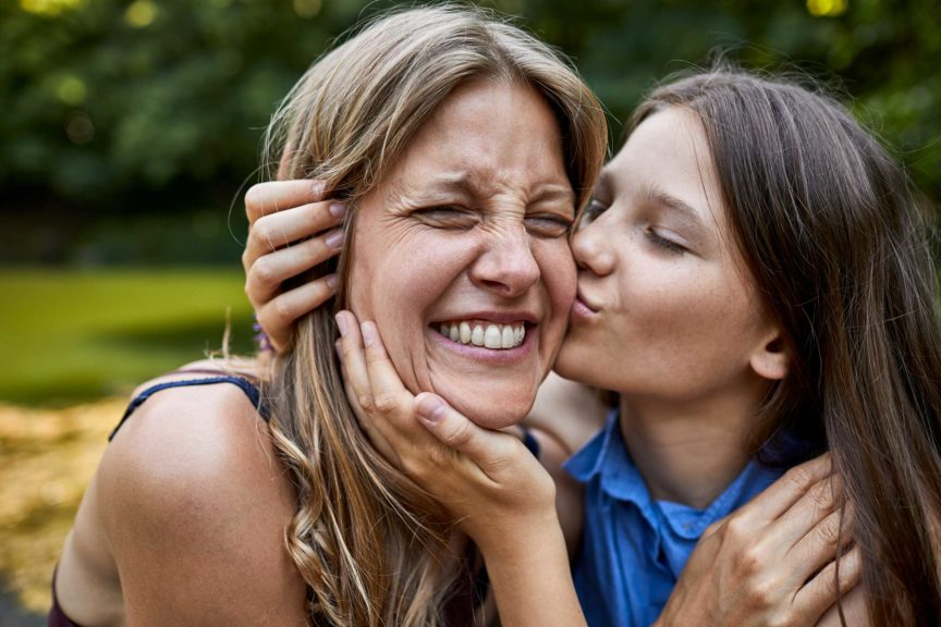 Girl hugging and kissing happy mother