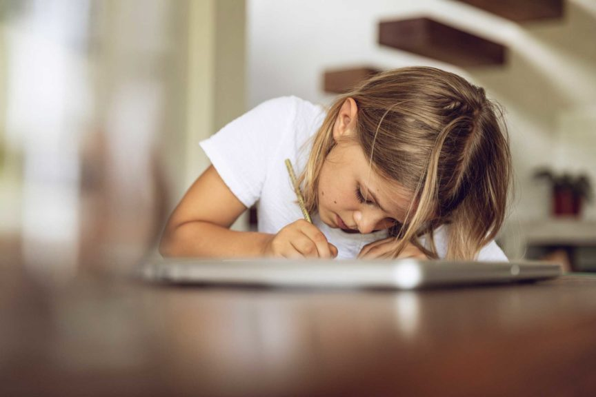 Girl sitting at table writing into diary