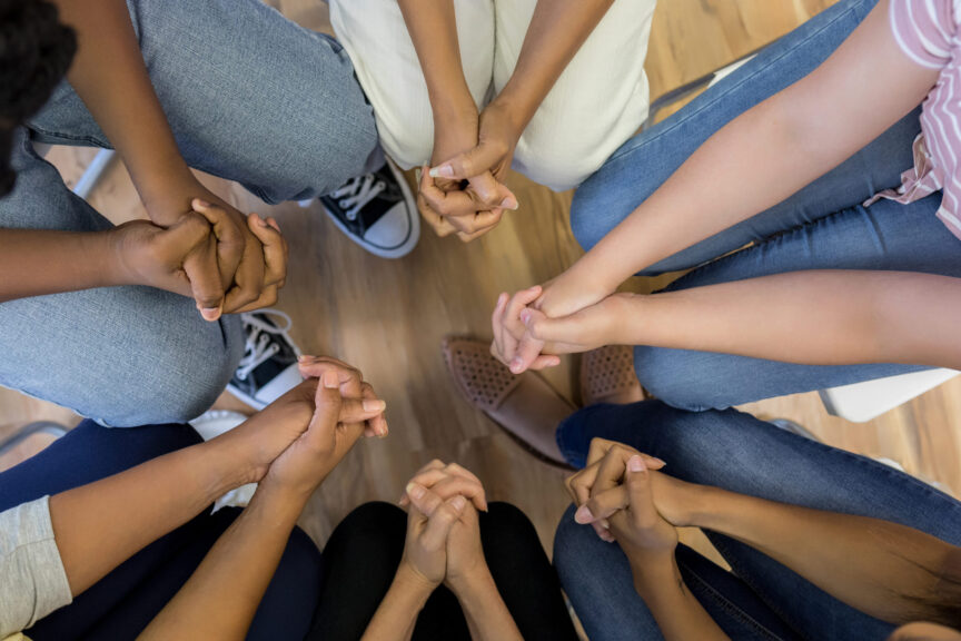 High angle view clasped hands of group sitting in circle