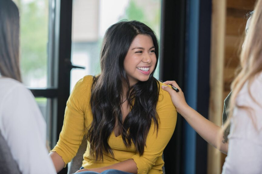 Hispanic woman smiling during support group