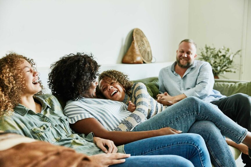 Laughing daughter embracing mother while sitting on couch with family in living room