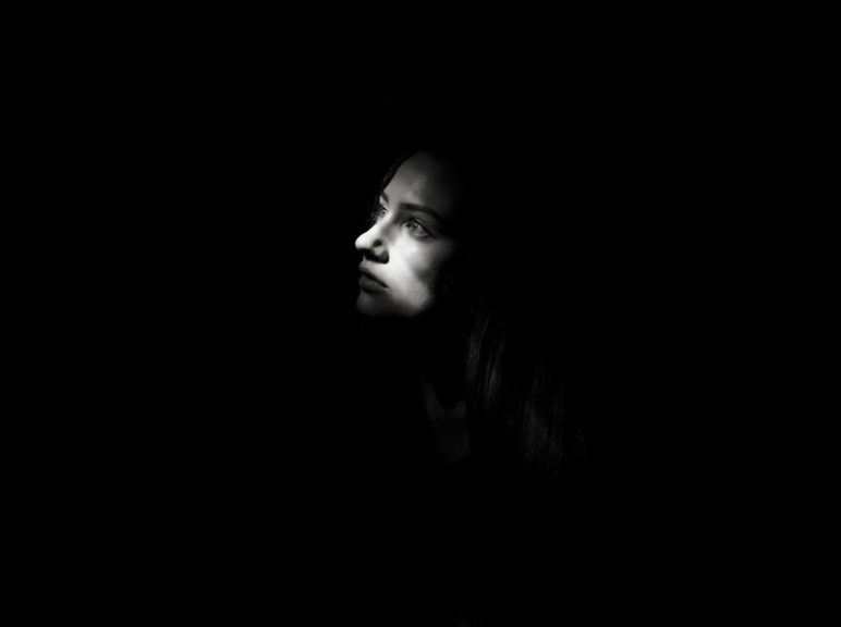 Light Falling On Thoughtful Woman In Darkroom