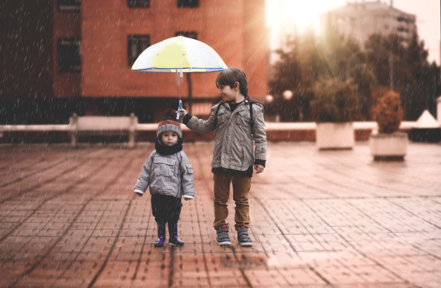 A little boy and his older brother protect themselves from the rain with an umbrella