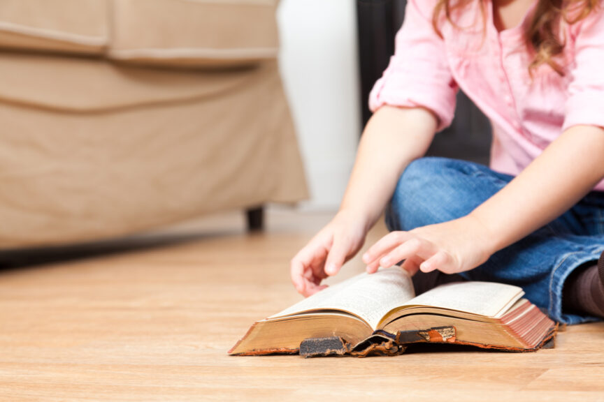 Little girl looking through an old Bible in living room