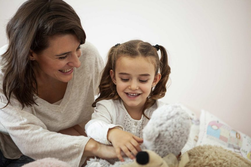 Mother and daughter playing with stuffed animals in bedroom