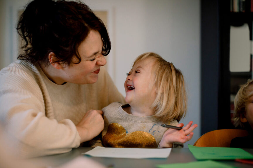 Mother-making-facial-expressions-while-playing-with-disabled-daughter-at-dining-table