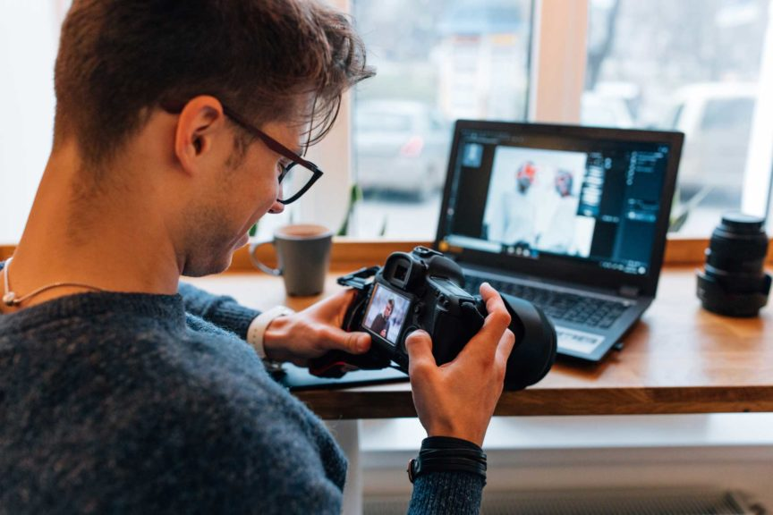 Photographer looks at photos in the professional camera at cafe with laptop