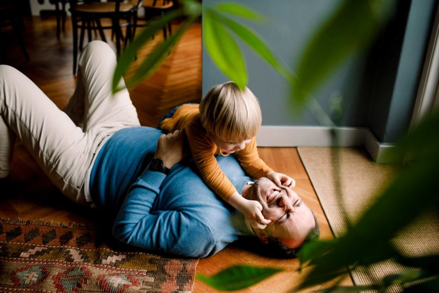 Playful daughter pinching cheerful father's cheeks on floor at home