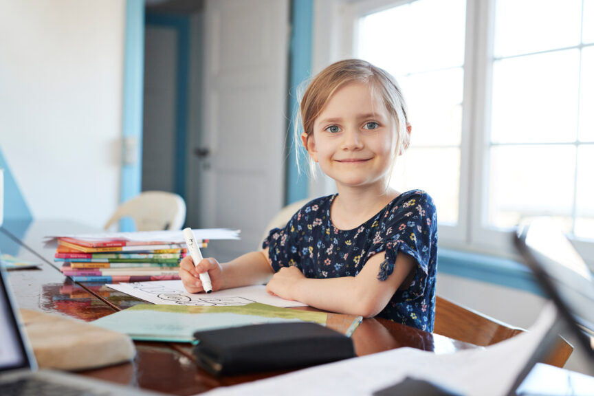 Portrait confident girl doing homework at dining table