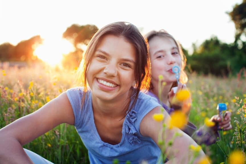 Portrait of girls sitting in field one blowing bubbles