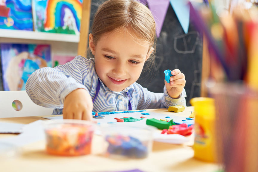 Portrait of smiling little girl working with plasticine in art and craft class