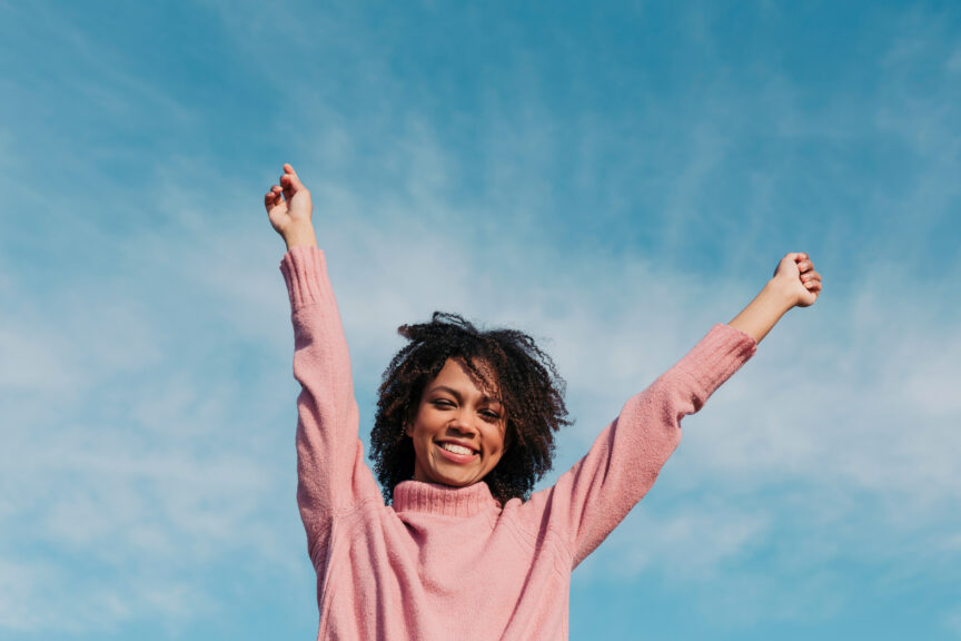 Portrait of smiling young woman against sky raising hands