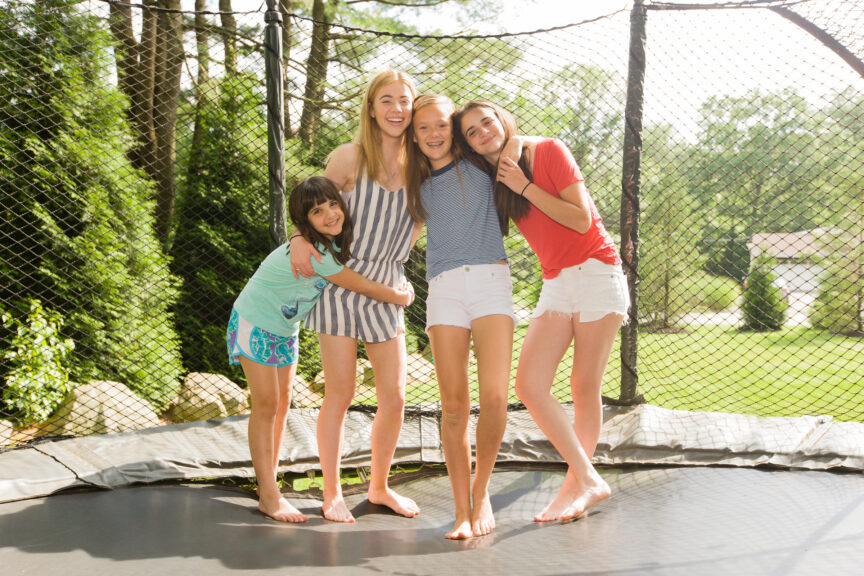 Sisters-hugging-on-a-trampoline-at-their-suburban-home