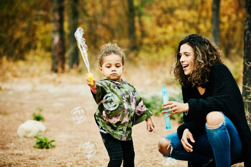 Smiling mother watching young daughter play with bubbles outside
