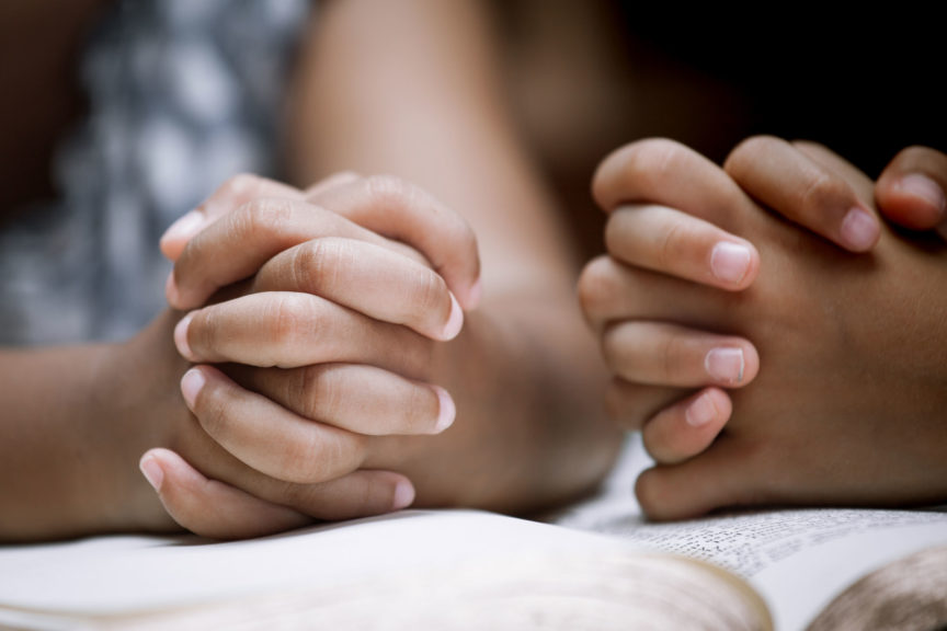 Two Little girl hands folded in prayer on a Holy Bible together