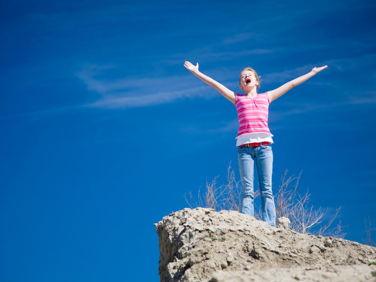 A young girl standing on a cliff with her arms outstretched
