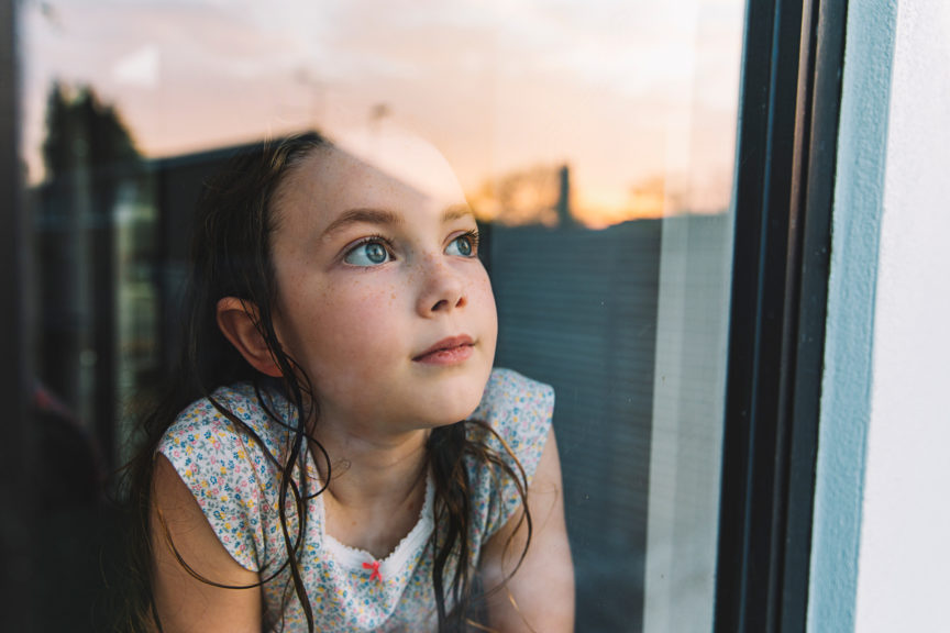 Young girl looking through window at sunset