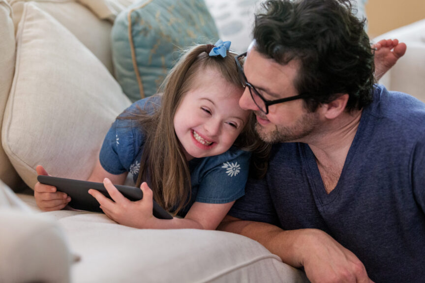 Young-girl-with-Down-Syndrome-giggles-with-dad