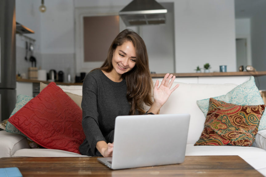 Young woman sitting on her couch, chatting on her laptop