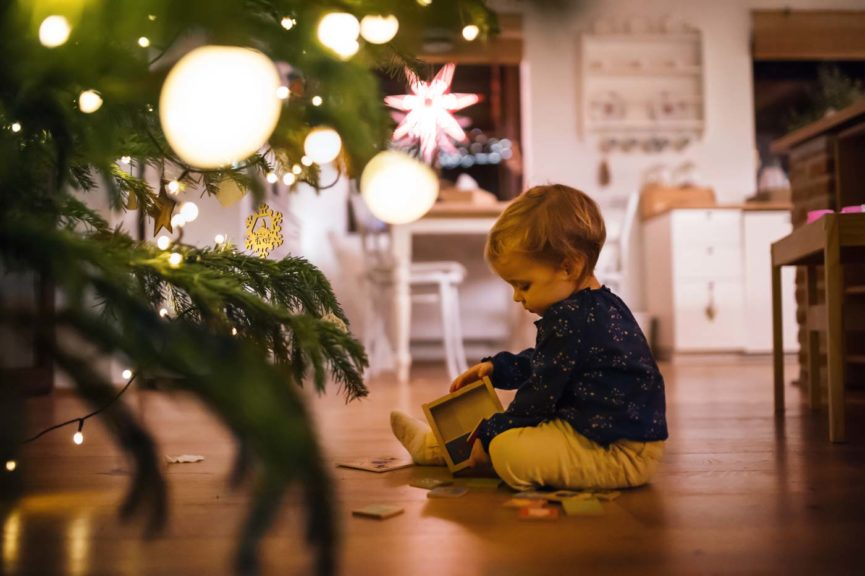 A small girl playing indoors on the floor at Christmas time