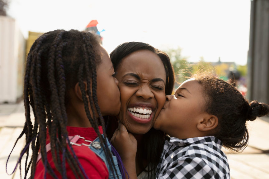 Affectionate daughters kissing mother