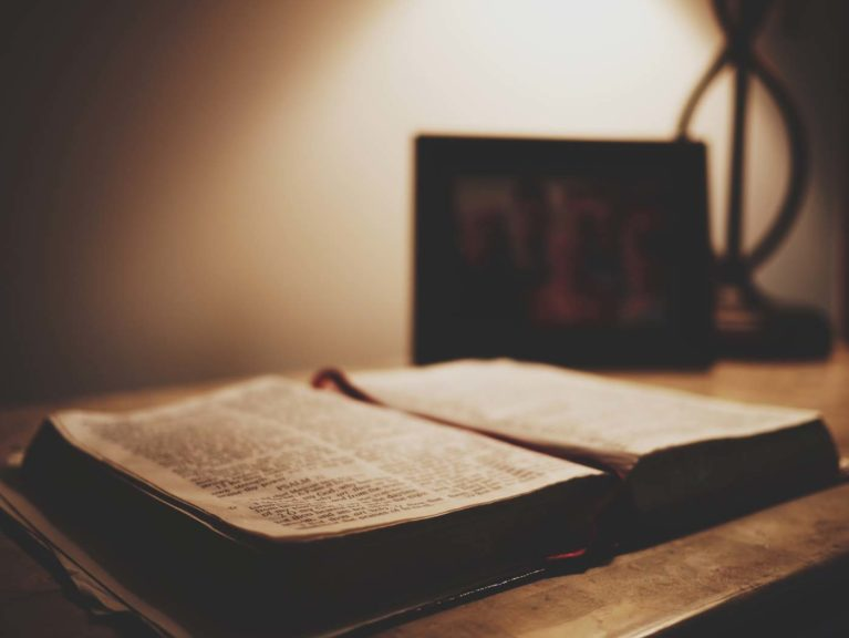 Bible open on nightstand in dark lighting