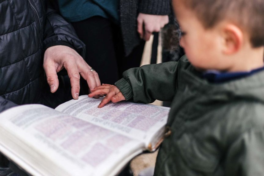 Boy and parent reading the bible together outside