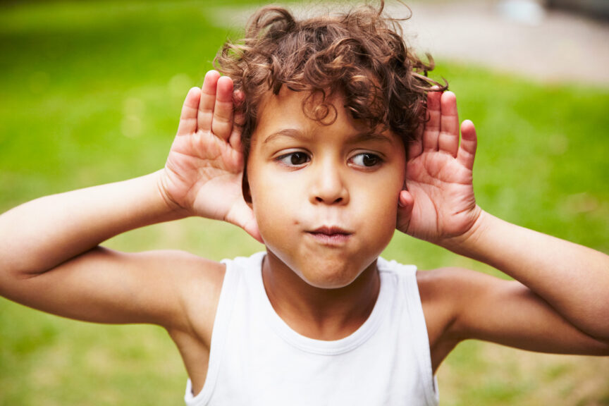 boy making faces and listening with ears