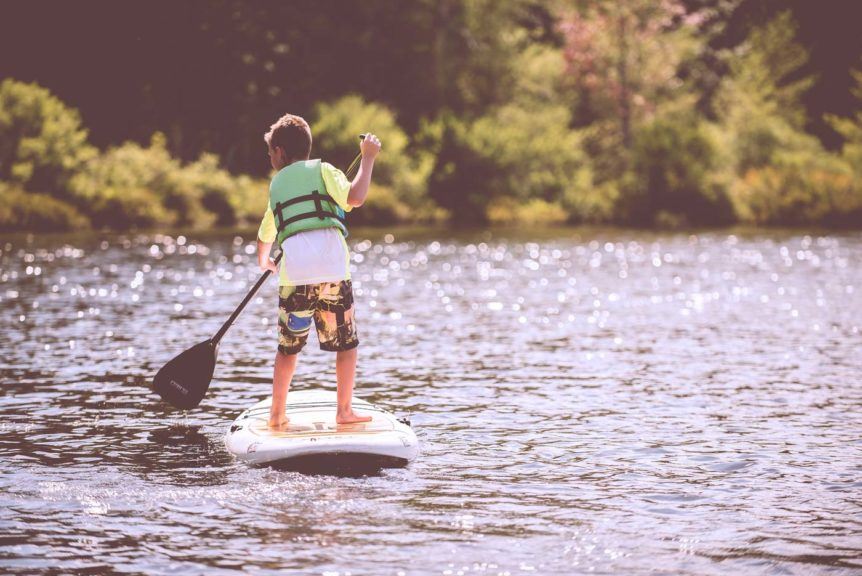 boy on a paddle board at the lake
