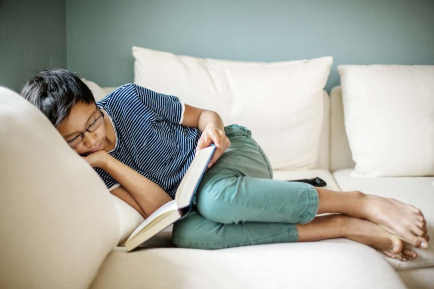 Boy reading book while lying on a sofa