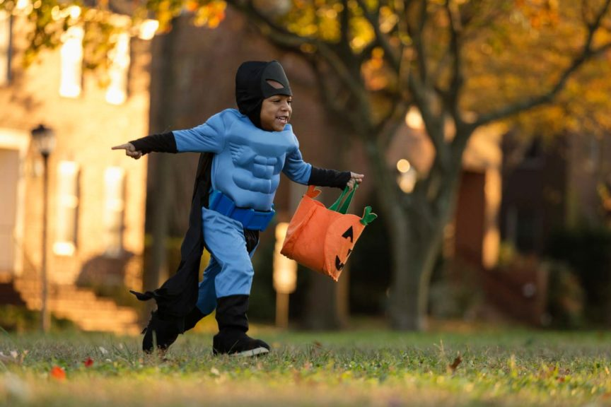 Boy running in superhero costume halloween