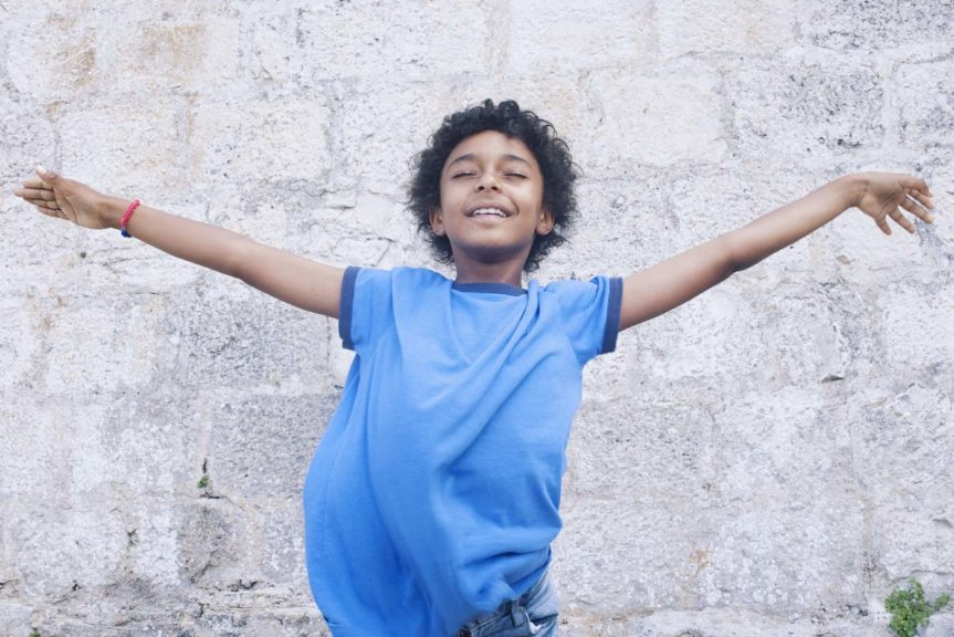 Boy standing with his arms outstretched, eyes closed