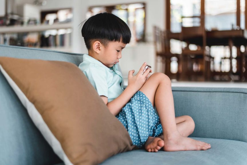 boy-using-smart-phone-living-room