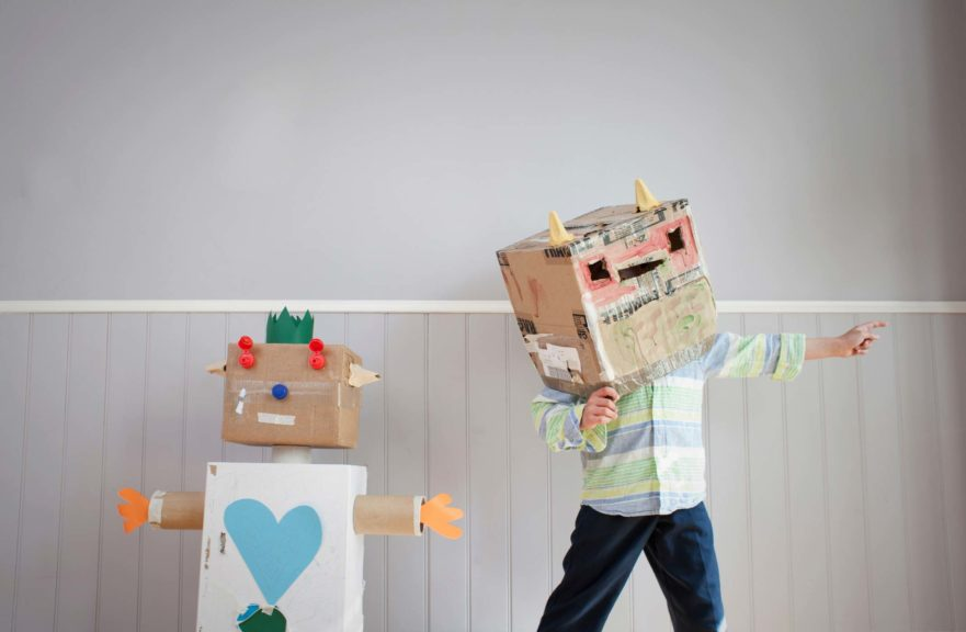 Boy with box covering head and homemade toy robot