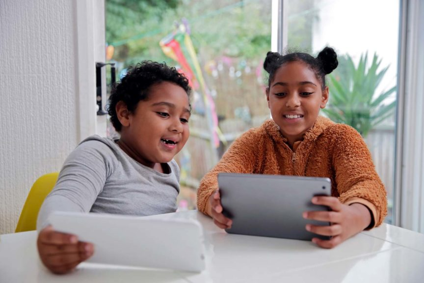 Brother and sister smiling and using digital devices