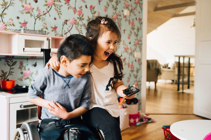 Cheerful sister watching video with autistic brother on smart phone at home